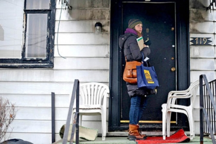Marlee Gallagher of Wilkinsburg walks along Wallace Avenue going door to door to try and collect signatures on a petition aiming to allow liquor licenses to be distributed in Wilkinsburg.