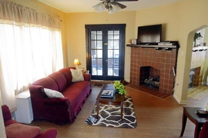 The living room features an original stone gas fireplace, wood mantel and French doors.