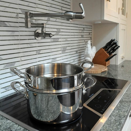 A swinging arm water faucet allows water to be added to cookware without having to carry it from the sink on the opposite side of the kitchen.