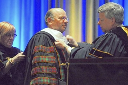 University of Pittsburgh Chancellor Mark A. Nordenberg, right, awards an honorary doctorate of public service to Jared Cohon, president of Carnegie Mellon University, on Friday.