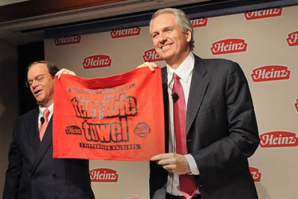 Bill Johnson, chairman, president and CEO of H.J. Heinz Co., presents a Heinz red Terrible Towel to Alex Behring, right, managing partner at 3G Capital, during a news conference announcing Berkshire Hathaway's and 3G Capital's acquisition of Heinz.