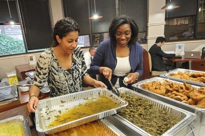 Simone Delerme, left, a third-year-law student and vice president of the Black Law Student Association works with Professor Tracey McCants Lewis to replace a pan of greens on the soul food sampler line at the Duquesne University law school.