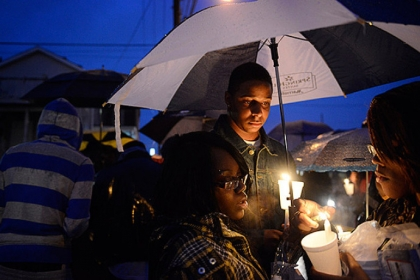 "Friends of Brian ""Lil Brucey"" Wright Jr., 26, including Ricardo Grimsley (center) pay their respects during a vigil Tuesday evening at the corners of Enterprise Street and Tangent Way in Larimer."