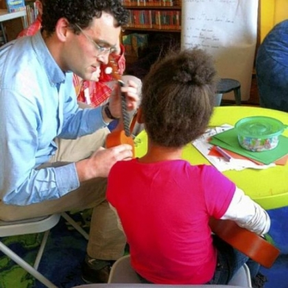 Dan Hensley (left) works with a 7-year-old ukulele enthusiast after school at the Carnegie Library's pop-up location in Allentown