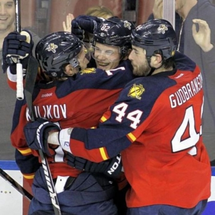 Florida's Tomas Kopecky, center, celebrates with teammates Dmitry Kulikov, left, and Erik Gudbranson (44) after Kopecky's third goal, an empty-netter against the  Penguins in a 6-4 Panthers win.