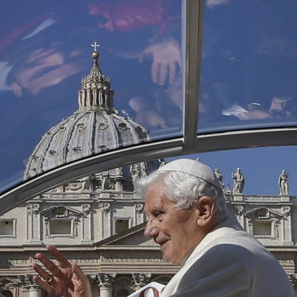 Faithful are reflected in the roof of Pope Benedict XVI's pope-mobile as he arrives to celebrate his last general audience in St. Peter's Square today.