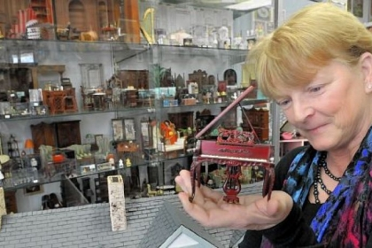 Debbie McManus, owner of Lynlott Miniatures Dollhouse Junction, examines a piano at the shop. The store is on Commercial Avenue in Aspinwall. Generally, if you can find it in your real house, you can buy it for your dollhouse.