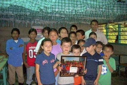 Jose Daniel, back row far left, with elementary school classmates holding a picture of Neil Armstrong Student Council in 2007, the first year the Student Council sold coffee to raise funds for scholarships in Honduras.