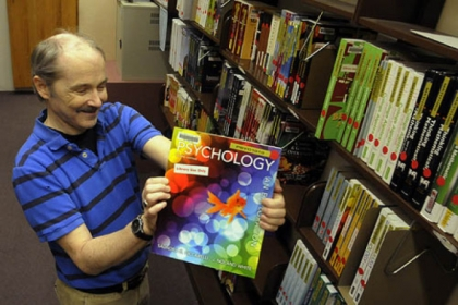 Bruce Johnston, access services librarian, holds one of about 200 textbooks that are on reserve at the Robert Morris University library. It has allowed about one in five students to access required textbooks without buying them.