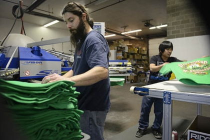 Joe Bonidie, left, and Aung N'yo pull Pittsburgh's official St. Patrick's Day Parade T-shirts off the presses Thursday at All Pro Embroidery and Screenprinting in Baldwin.