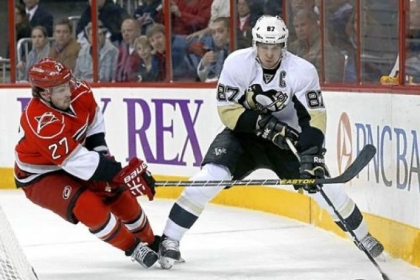 Sidney Crosby handles the puck behind the Hurricanes net.