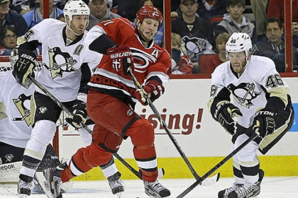 Carolina's Jordan Staal, center, chases the puck against Penguins' Brooks Orpik, left, and Joe Vitale during the first period of last night's 4-1 Carolina victory.