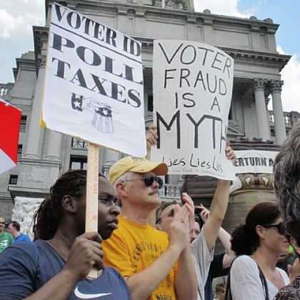 Demonstrators hold signs at a rally against the voter ID law in July in Harrisburg.