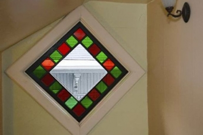 A stained-glass window on the second-floor landing casts red and green light.