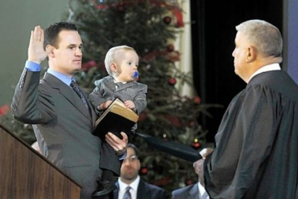 Luke Ravenstahl holds son, Cooper, on Jan. 4, 2010, as he takes the oath of office for Mayor of Pittsburgh, given by his father, District Judge Robert Ravenstahl Jr.