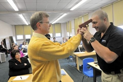 In this three-photo sequence, Sam Rosenberg, black shirt, shows North Catholic High School religion teacher Greg Evans, left, how to disarm a gun-wielding intruder at close range during a session at the Troy Hill school on Monday.