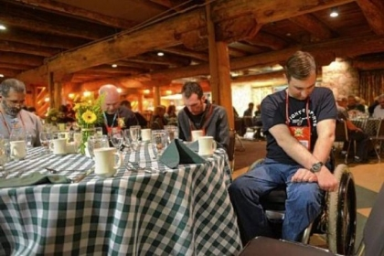 Erik Burmeister, right, a former Army National Guard member from Williamsport, Pa., bows his head for a prayer during a Wounded Warriors retreat banquet dinner held at Seven Springs Mountain Resort.