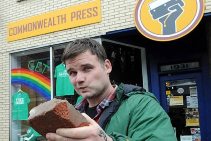 Dan Rugh, owner of Commonwealth Press, with the brick that broke a front window (since fixed) at his East Carson Street business.