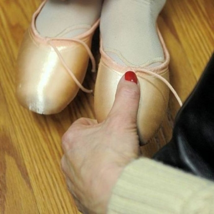 A Pittsburgh Ballet School student is checked to see if her first pair of pointe shoes fit correctly.