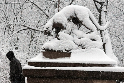 Snow covers the panther statues at the Panther Hollow Bridge in Schenley Park early wednesday morning.