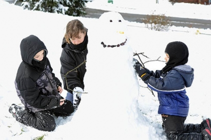 Tiffany Grimes of Franklin Park, makes a snowman with her sons, Luke, left, 8, and Hunter, 5, in their front yard today.