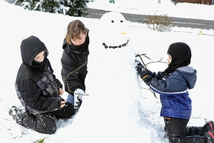 Tiffany Grimes makes a snowman with her sons, Luke, left, 8, and Hunter, 5, in their front yard in Franklin Park after the boys&#039; school was closed due to a heavy snowstorm  Wednesday.