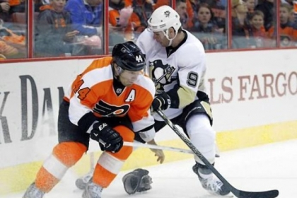 The Flyers' Kimmo Timonen, left, loses one of his gloves as he battles for the puck with the Penguins' Pascal Dupuis.