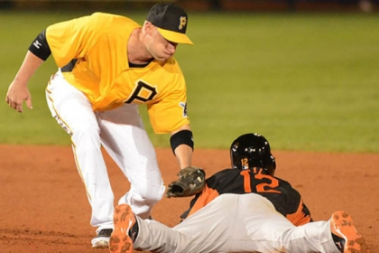 Baltimore&#039;s Alexi Casilla slides under the tag of  Pirates shortstop Clint Barmes.