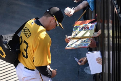 Fans reach through the fence to get autographs from Travis Snider Friday in Bradenton, Fla.