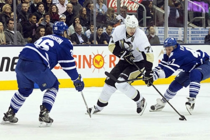 Evgeni Malkin takes the puck between Toronto&#039;s Carl Gunnarsson, left, and Leo Komarov in the Penguins&#039; 5-4 shootout win Saturday night.