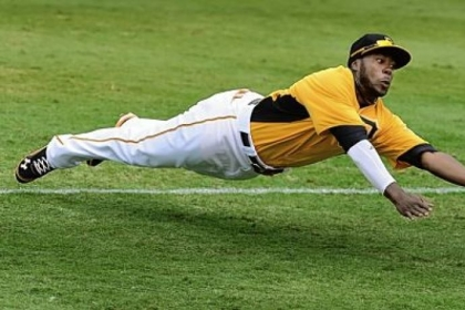 Second baseman Josh Harrison dives for a ball hit by Minnesota's Jamey Carroll in the Pirates' 5-4 exhibition loss to the Twins Saturday at McKechnie Field in Bradenton, Fla.
