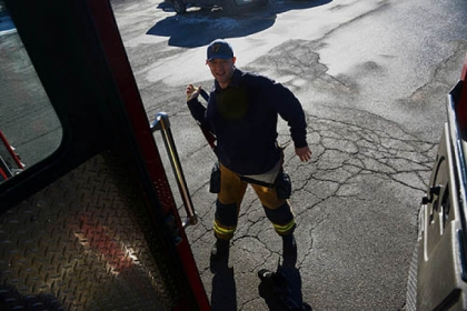 After receiving the call about sparking wires, firefighter Dan Reiser puts on his gear in the parking lot. When the firefighters return later to the grocery store, their cart is still there.