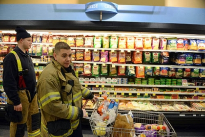 Lt. John Gardell, center, and firefighter Dan Reiser, return to Giant Eagle to find their cart exactly where they left it on Friday, Jan. 18, 2013.