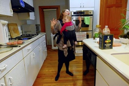 Like other moms who work outside of the home, Stefanie Small of Squirrel Hill says the most stressful part of her day is when she returns home from work as a geriatric social worker to care for her three children. She uses a carrier to hold 11-month-old Aria as she makes dinner.