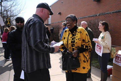McKeesport committeewoman Laura Jenkins gets some candidate information from Joe Bendel as she enters the IBEW building on the South Side to vote during the Allegheny County Democratic Committee endorsement meeting Sunday.
