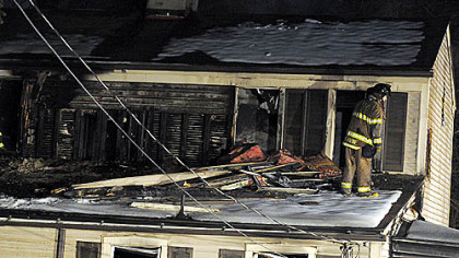 A Pittsburgh firefighter takes part in the investigation of a two-alarm blaze this morning at 1920 Plateau St. in Carrick.