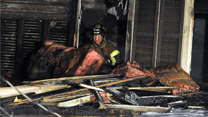 A firefighter removes debris from the burned home in Carrick.