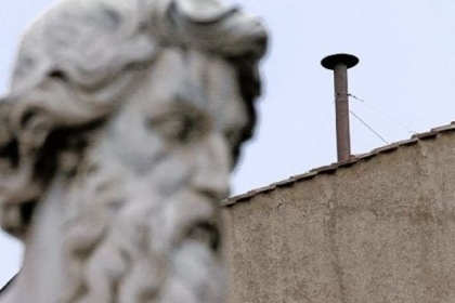 A statue dwarfs the chimney on the roof of the Sistine Chapel, where cardinals will gather today to elect the new pope during the conclave at the Vatican.