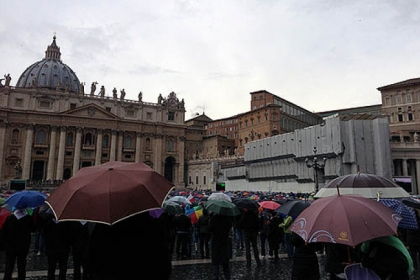 Spectators watch black smoke rising as rain falls this morning in Vatican City.