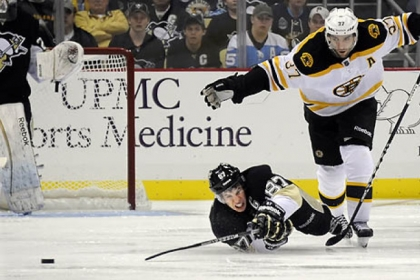 Boston&#039;s Patrice Bergeron trips Sidney Crosby going for the puck in the third period Tuesday.