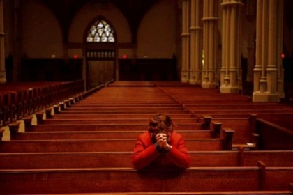 A woman kneels to pray Wednesday for Pope Francis at St. Paul Cathedral in Oakland.