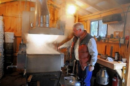 Dan Wingard checks on the maple syrup boiling in a building at his home in Gibsonia.