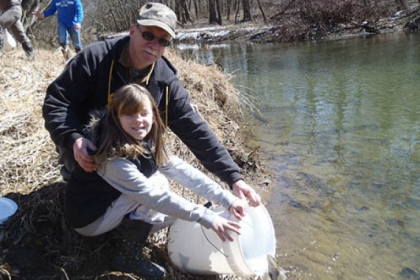 Makayla Boda, 9, and her grandfather Carl Dranzo of Roscoe stock trout at Loyalhanna Creek.
