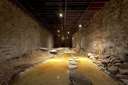 "From the Mattress Factory exhibition ""Feminist And ..."": Betsy Damon's ""Water Rules Life Pittsburgh: Seeking Lost Rivers, Living Waters of Larimer"" (2012), including sand, water, rocks, burlap, concrete, topographical map, audio, video."