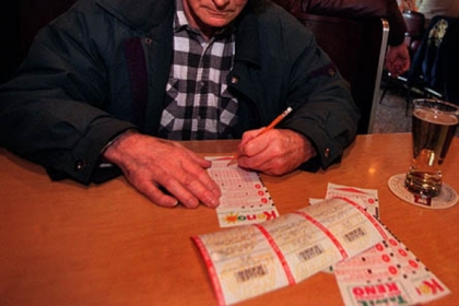 A man fills out a Keno ticket at a bar in West Virginia.