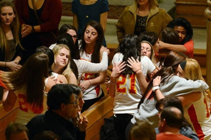 Members of the Seton Hill University women's lacrosse team, wearing their team jerseys, embrace on Sunday evening during a memorial Mass for Kristina Quigley, their pregnant coach, and Anthony Guaetta, the driver of their bus, who died Saturday in a crash on the Pennsylvania Turnpike.