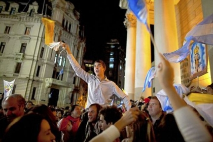 Faithful wave Vatican and Argentinian flags Wednesday as they sing outside the Metropolitan Cathedral in Buenos Aires, Argentina. Latin Americans reacted with joy on Wednesday at news that Argentine Cardinal Jorge Mario Bergoglio was elected pope. Cardinal Bergoglio, who chose the name Pope Francis, is the first pope from the Americas.