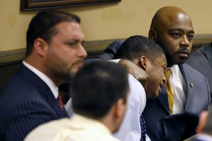 Defense attorney Walter Madison, right, holds his client, 16-year-old Malik Richmond, while defense attorney Adam Nemann, left, sits with his 17-year-old client Trent Mays, foreground. Both teens were found delinquent this morning for rape.