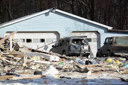 A damaged garage and vehicles are adjacent to a house explosion  in Clearfield Township, Cambria County today.