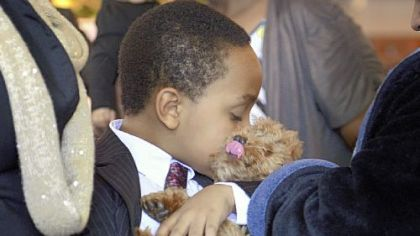 Zaire Brown, kisses his dog Leo on Tuesday at his mother's funeral.  Services for Ka'Sandra Wade were held at the Greater Mount Zion Church of God in Christ in Farrell, where Wade grew up.